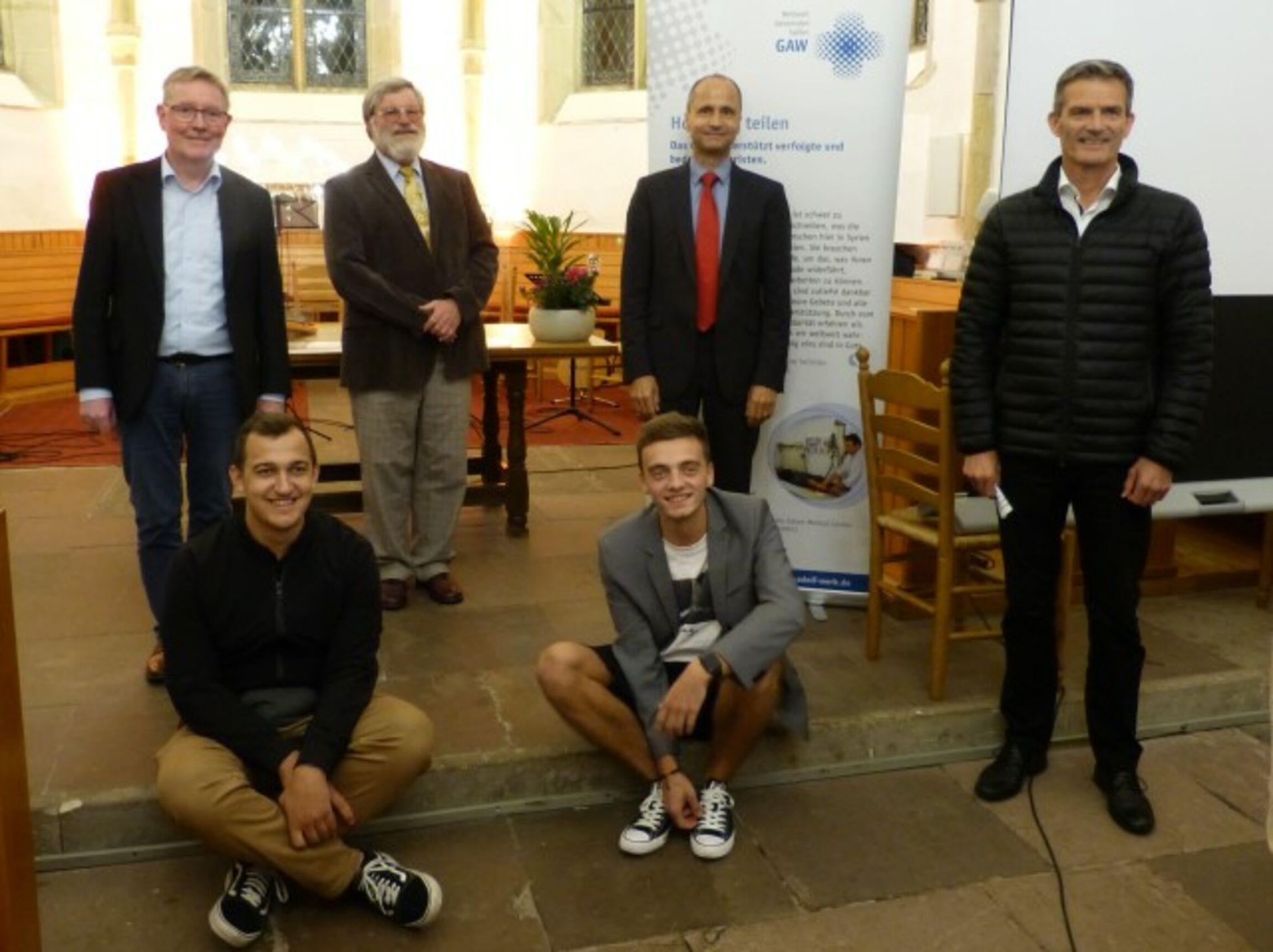 v.l.n.r.: Pastor Behmenburg, Pastor Giesecke von Bergh, OKR Stelter, Generalsekretät Haaks; sitzend: Stipendiaten Levente Dinka und Andrej Laschko