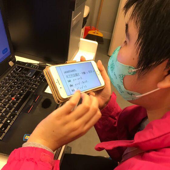 Ein blinder Schüler mit seinem Handy, über das er jetzt die Unterrichtsmaterialien empfängt