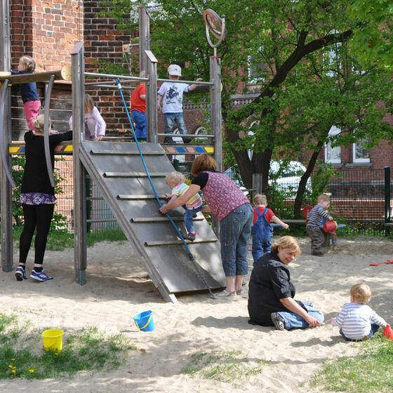 Erzieherinnen und spielende Kinder auf dem Außengelände.