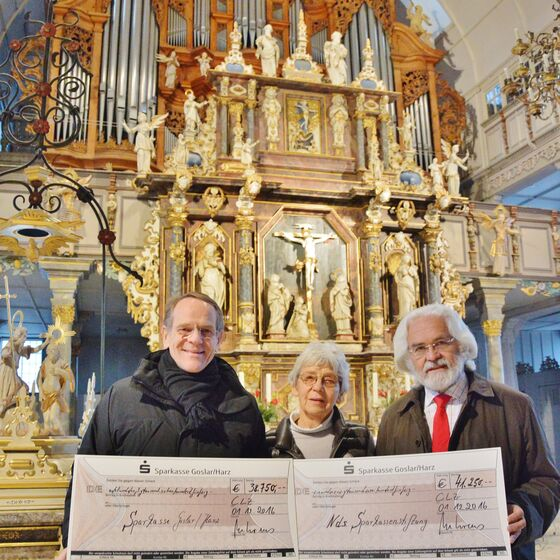 Darum gibt es auch gleich zwei Fotos von der Übergabe vor der Orgel