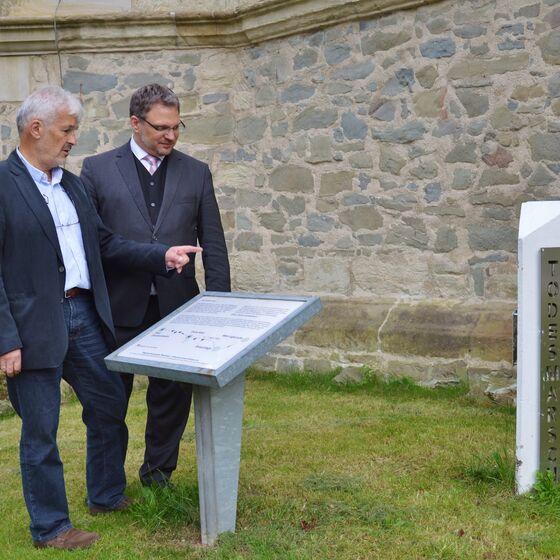 Firouz Vladi und André Dittmann an der Gedenktafel und Stehle vor der Kirche