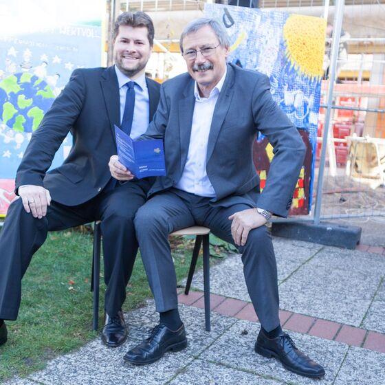 Bezirksbürgermeister Grunenberg und Ratsherr Spiegelhauer testen den neuen Stuhl