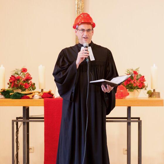 Pastor Vasel mit Bauhelm