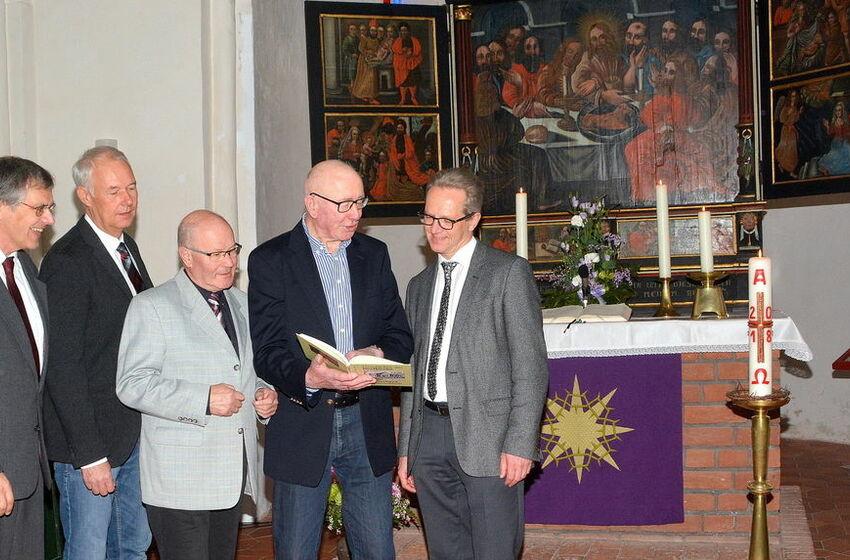 Blick ins Buch: Martin Labohm (2.v.r.) mit Superintendent Tido Janssen (r.), Ewald Hennek (3.v.l.) und Peter Junker (2.v.l., Print Media GmbH) sowie Pastor Bernd Battefeld (l.).Foto: Gerd-Arnold Ubben