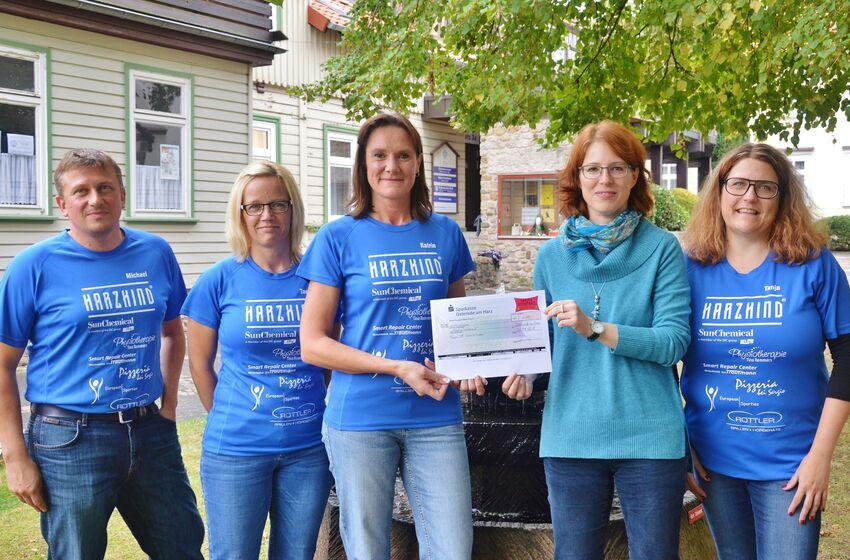 Die Harzkinder Tanja Remmers, Tanja Balkart, Katrin Bruns und Michael Bruns übergeben Susanne Mende einen Scheck über 1000 Euro