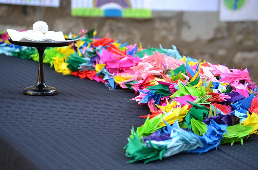 Eine bunte Girlande aus gefalteten Papierkranichen erinnert an die Opfer