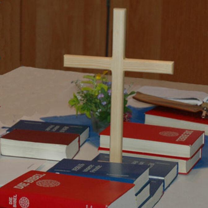 Ein Holzkreuz mit mehreren Bibeln auf einem Tisch.